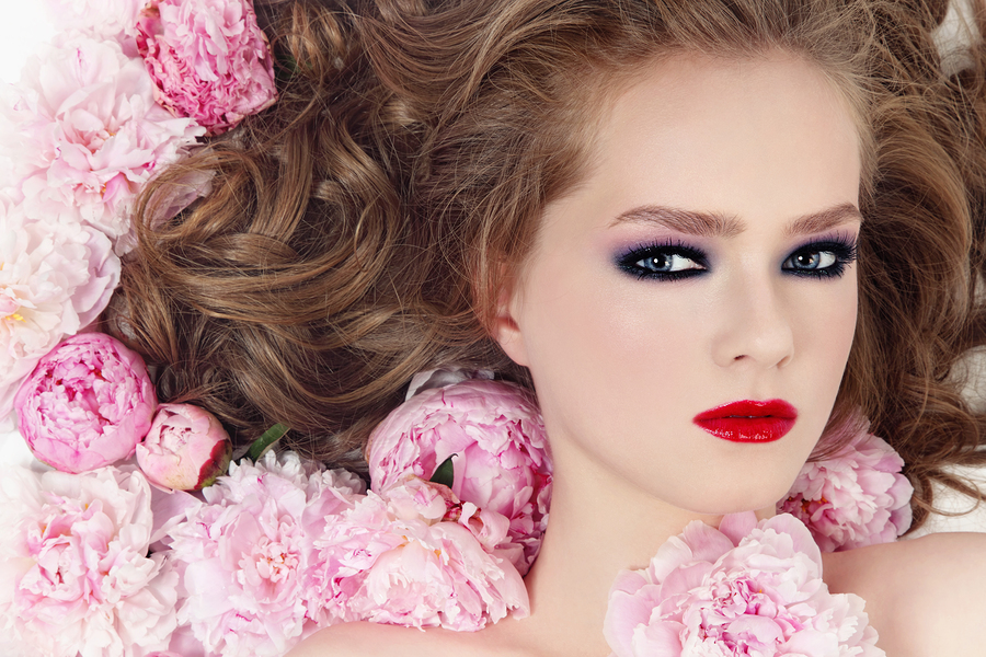 Portrait of young beautiful girl with stylish make-up and pink f
